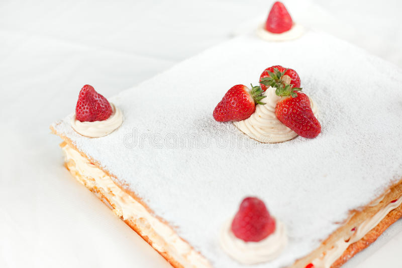 Strawberry Millefeuille. A big strawberry Millefuille with lemon custard and icing sugar on top with fresh strawberries. Shallow depth of Field on Strawberries stock image
