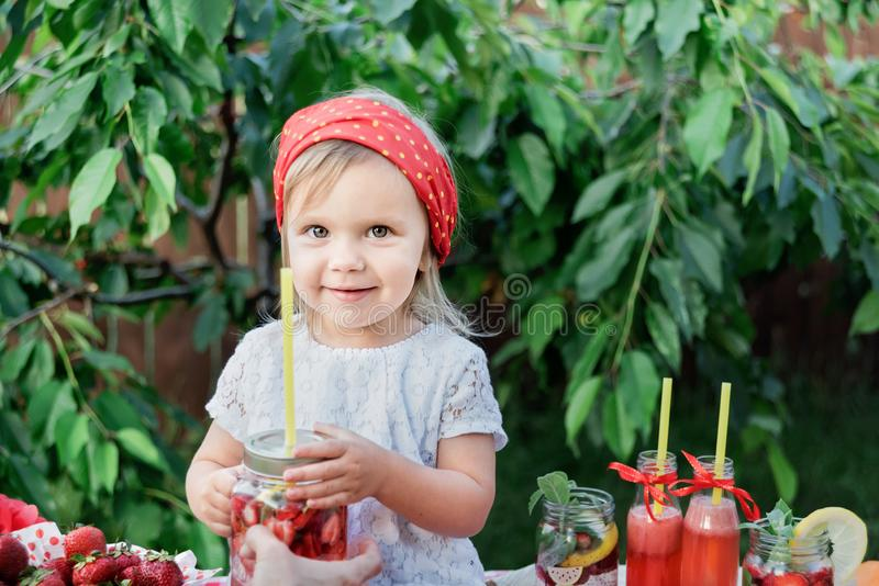Strawberry and mint infused detox water. strawberry lemonade with ice and mint as summer refreshing drink in jars. Cold soft. Lemonade Stand. Adorable little stock images