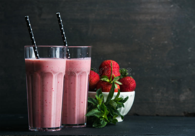 Strawberry and mint smoothie in tall glasses, bawl of fresh berries on dark rustic wood background stock photography