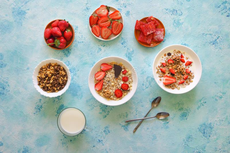 Strawberry, muesli, milk and Turkish delight on a turquoise table. stock photo