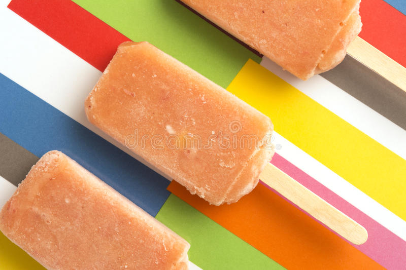 Strawberry, Orange, Pineapple, Mango Fruit Popsicles on Colorful royalty free stock photography