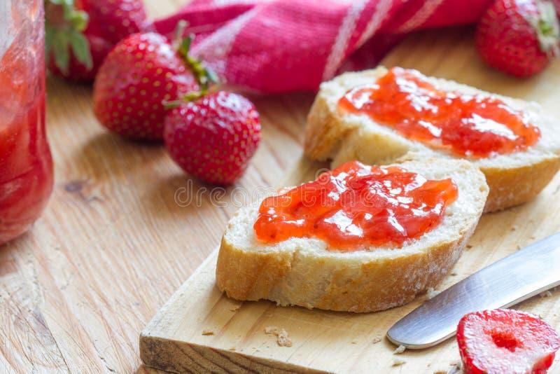 Strawberry organic homemade jam on bread. Closeup stock photography