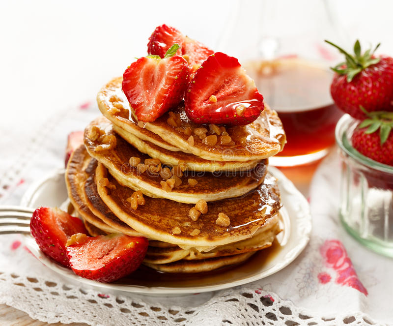 Strawberry pancakes with addition of maple syrup and caramel topping. Pancakes with fresh strawberries, maple syrup and caramel topping royalty free stock photos