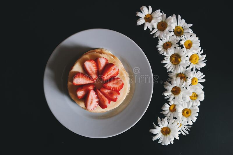 Strawberry pancakes and flowers royalty free stock images
