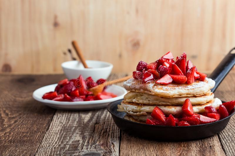 Strawberry  pancakes,  summer brunch rural table. Brunch, favorite morning meal. Homemade berry  pancakes, fresh summer dessert with strawberries, honey and royalty free stock photos
