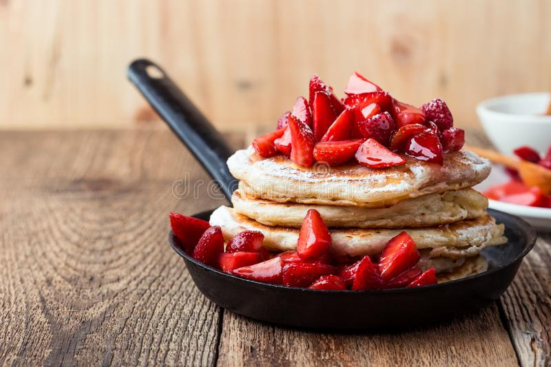 Strawberry  pancakes,  summer brunch rural table. Brunch, favorite morning meal. Homemade berry  pancakes, fresh summer dessert with strawberries, honey and stock image