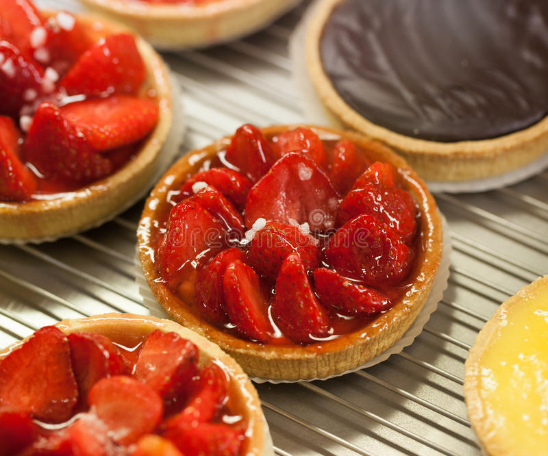 Strawberry pie chocolate cake lemon tart. Fruit pies and sweet tarts in display at the bakery royalty free stock photography