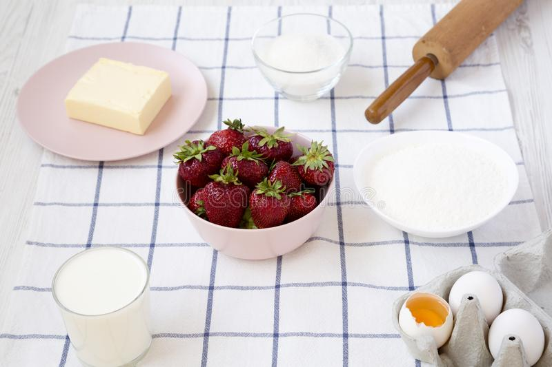 Strawberry pie ingredients flour, eggs, butter, milk, sugar, strawberry, side view. Cooking strawberry pie or cake stock image