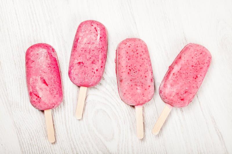 Strawberry popslice icecream on light background. Strawberry popslice icecream on light wooden background royalty free stock photography