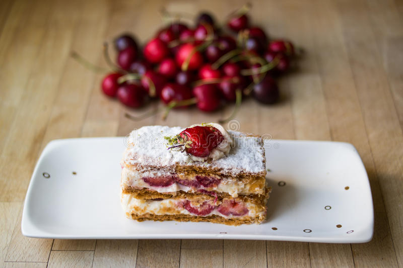Strawberry puff mille-feuille with cherry. From patisserie royalty free stock photography