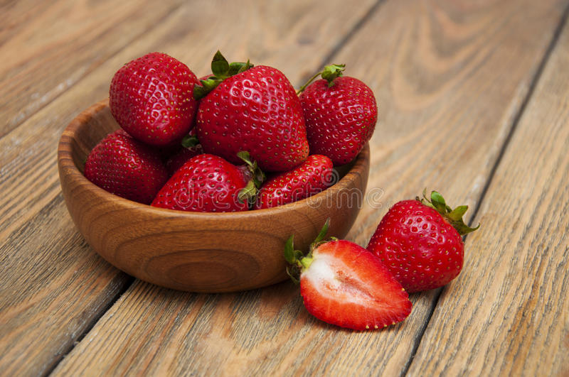 Strawberry. Ripe red strawberries in a wooden plate on a wooden background royalty free stock image