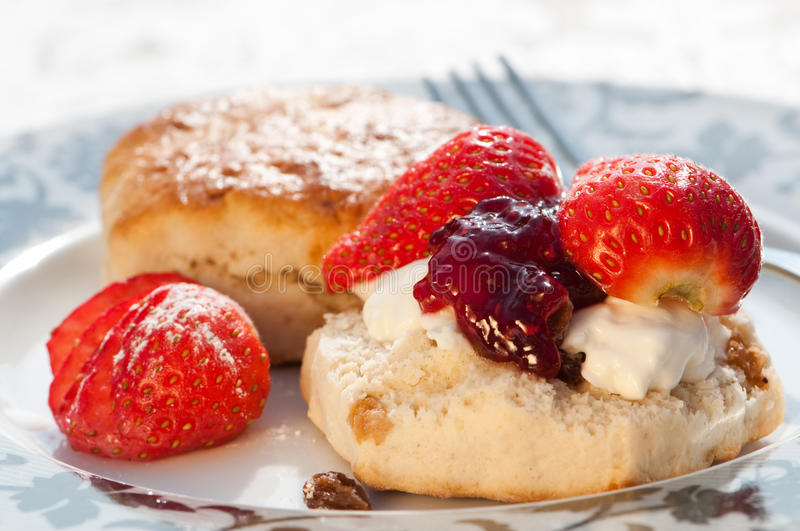 Strawberry Scones. Plate of strawberry scones with clotted cream and jam royalty free stock image