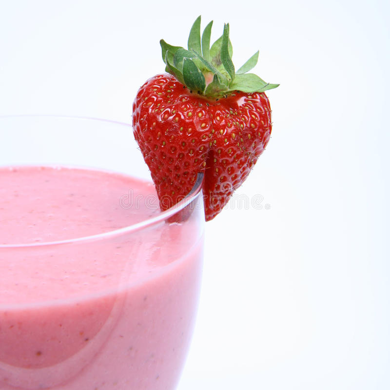 Strawberry shake. In a glass decorated with a strawberry on white background stock photo