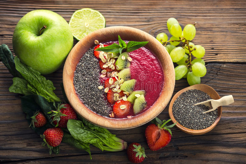 Strawberry smoothie in the bowl. With fruits and chia seeds royalty free stock photo