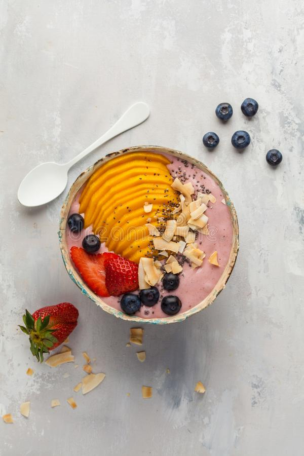 Strawberry smoothie bowl with mango and coconut, top view, copy. Berry smoothie bowl with mango and coconut, top view, copy space stock photo