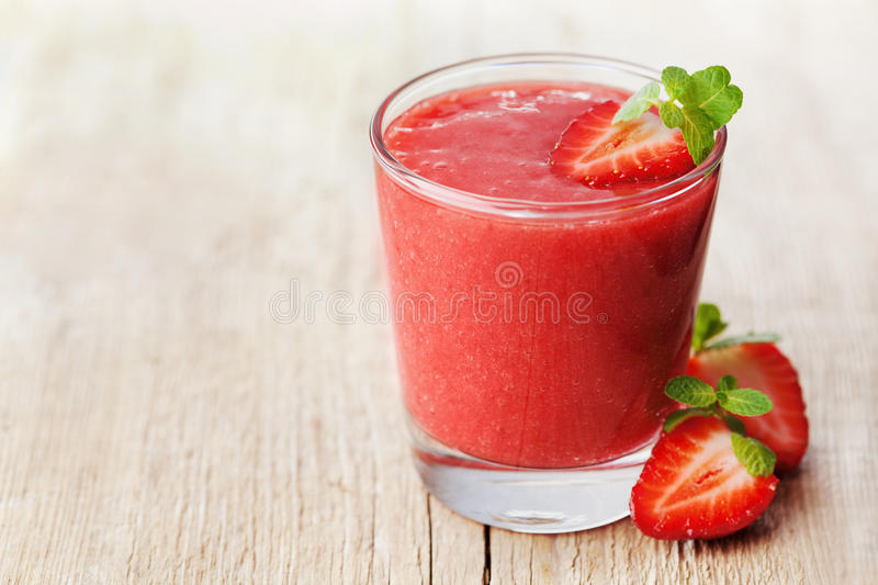 Strawberry smoothie in a glass decorated with mint leaves on rustic background, fresh fruit juice, detox food stock images