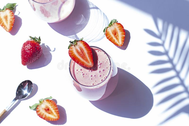 Strawberry smoothie in a glass on the white background. Healthy summer breakfast royalty free stock photos
