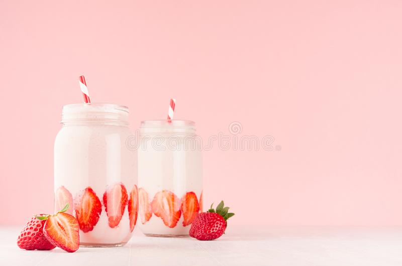 Strawberry smoothies in retro glass jars with bright sliced berries, straws on light, soft, pink background, copy space. Strawberry smoothies in retro glass royalty free stock image