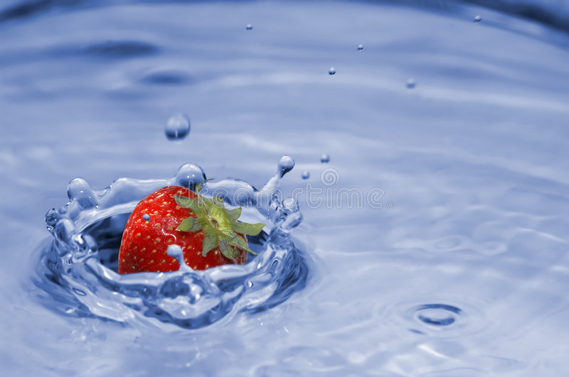 Strawberry splash. Fresh colored splash with strawberry royalty free stock photography