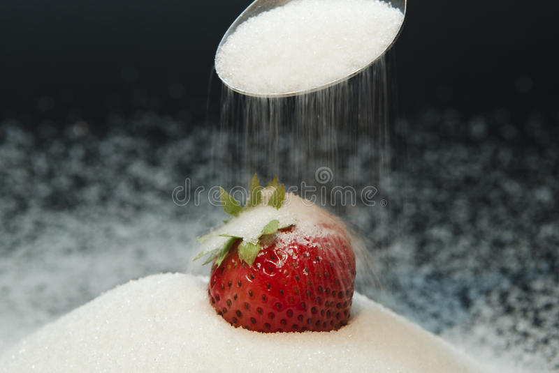 Strawberry on a spoon. With sugar on black background royalty free stock image