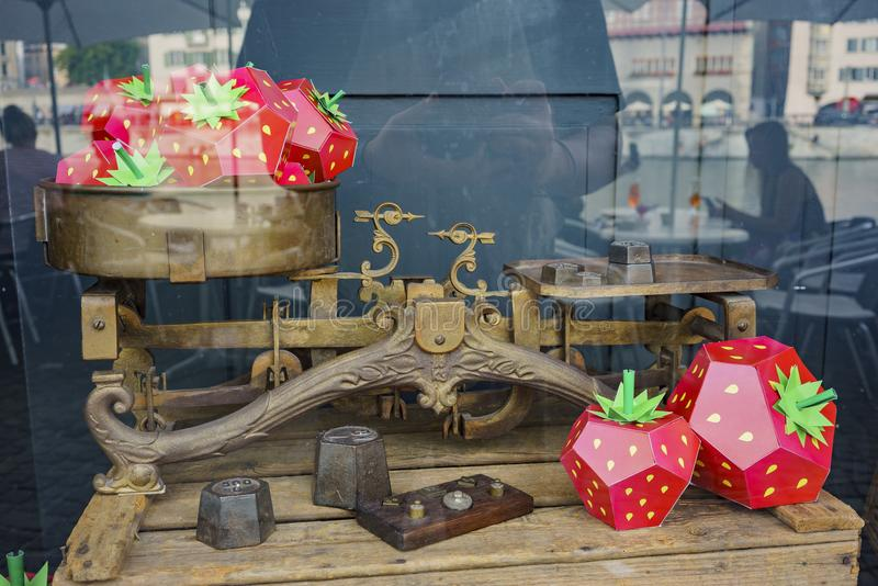 Strawberry style object and old Balance scales. Zurich, JUL 15: Strawberry style object and old Balance scales on JUL 15, 2017 at the historical Zurich city royalty free stock photography