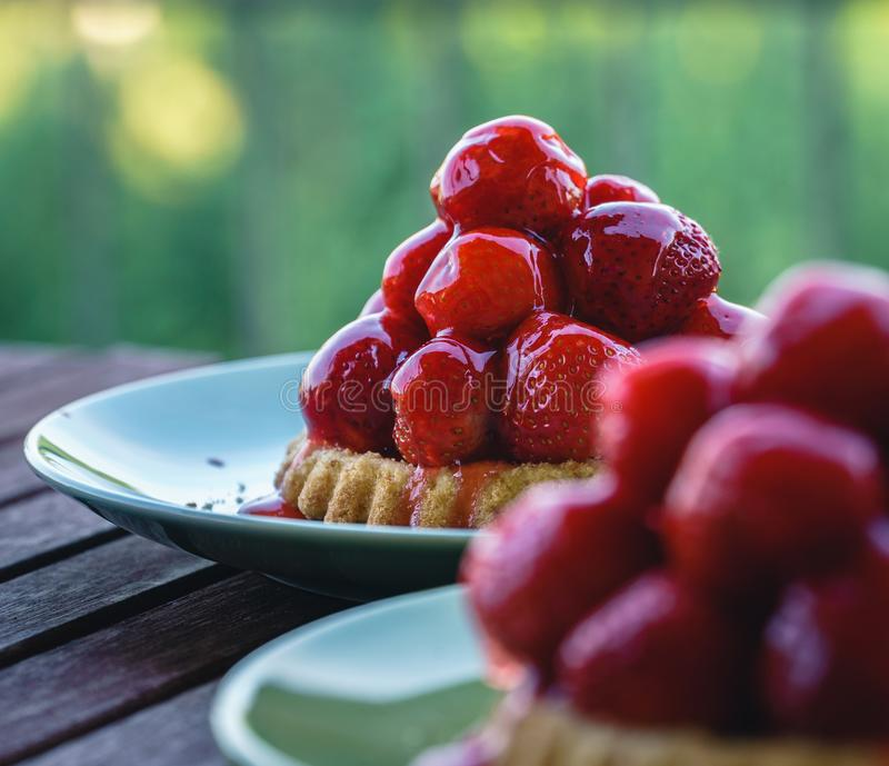 Two tiny strawberry tarts on green plates - Close-up stock photo