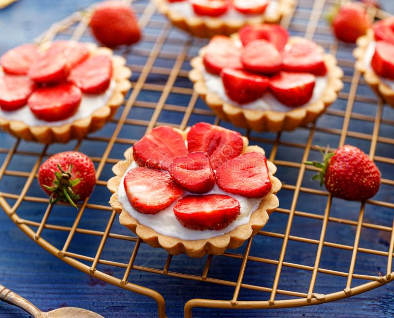 Strawberry tarts, small shortbread tarts with the addition of cream cheese, fresh strawberries  on a cooling tray royalty free stock photo