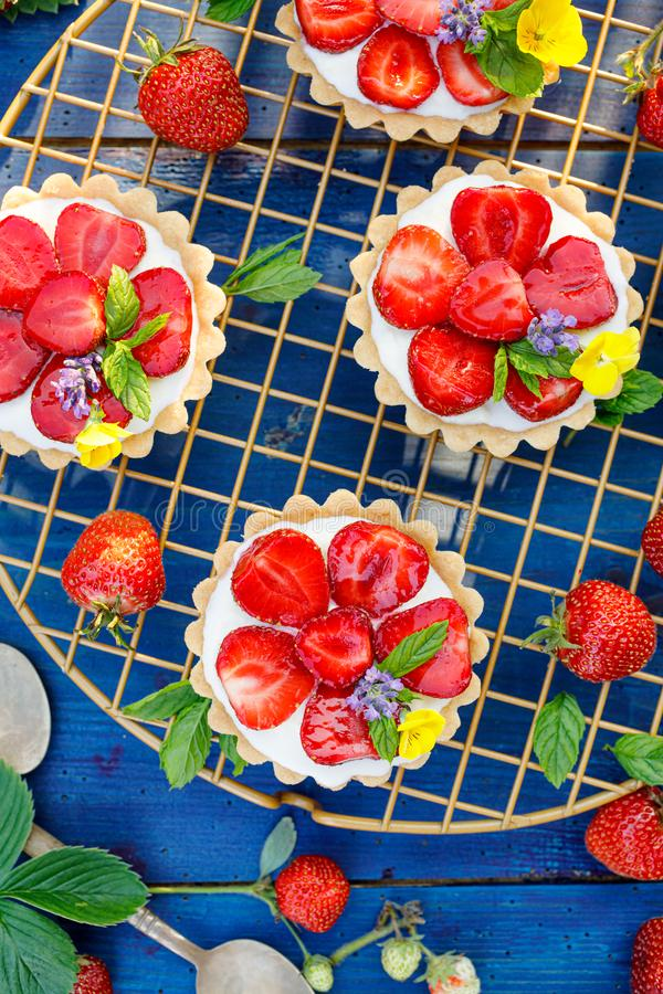 Strawberry tarts, small shortbread tarts with the addition of cream cheese, fresh strawberries and mint on cooling tray royalty free stock photo
