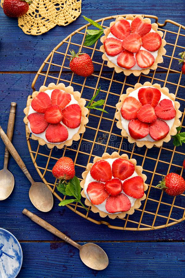 Strawberry tarts, small shortbread tarts with the addition of cream cheese, fresh strawberries and mint on cooling tray stock image