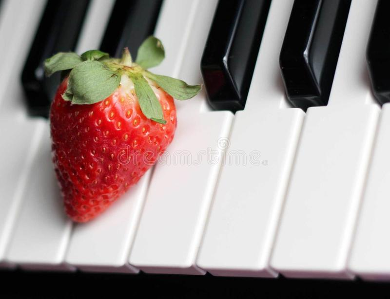 Strawberry on Top of Piano Keys royalty free stock photos
