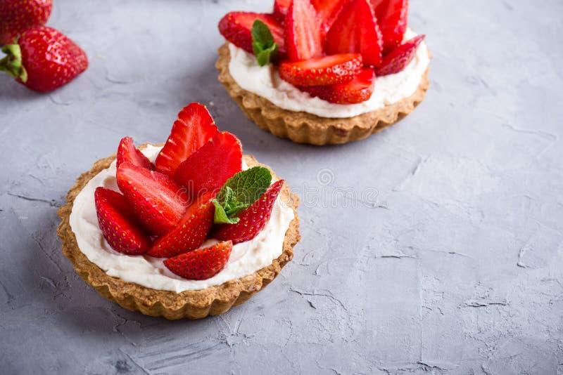 Strawberry vanilla cream cheese tarts over light gray table. Strawberry vanilla cream cheese tarts over light gray background royalty free stock photo