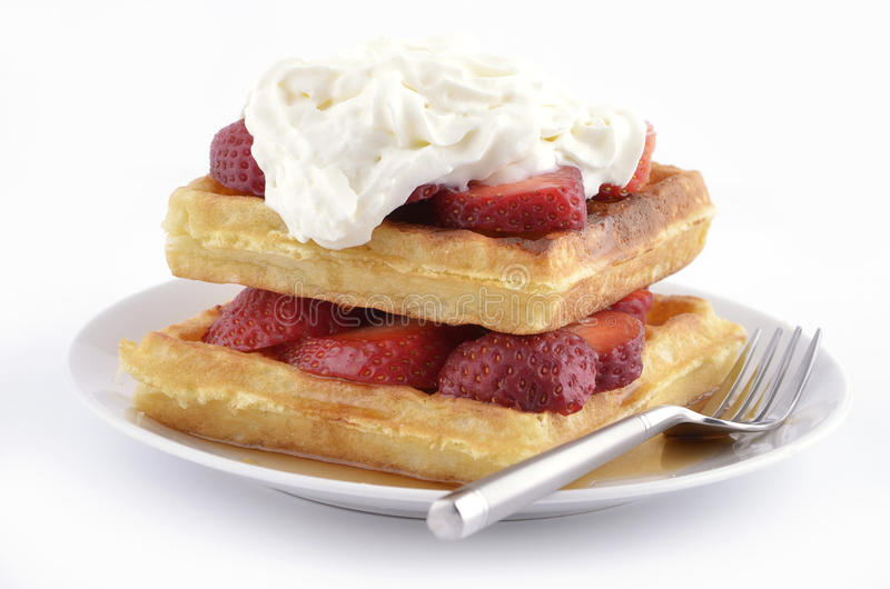 Strawberry waffles. Belgian waffles with fresh strawberries, maple syrup and whipped cream on white plate royalty free stock image