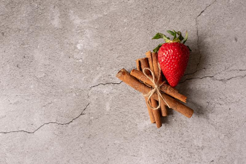 Strawberry, whole and halved with green leaves and three cinnamon sticks on a neutral white background royalty free stock images