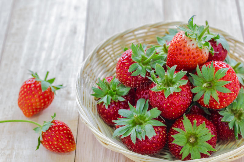 Strawberry in wood basket. Close up shot Strawberry in wood basket on wooden table royalty free stock photos