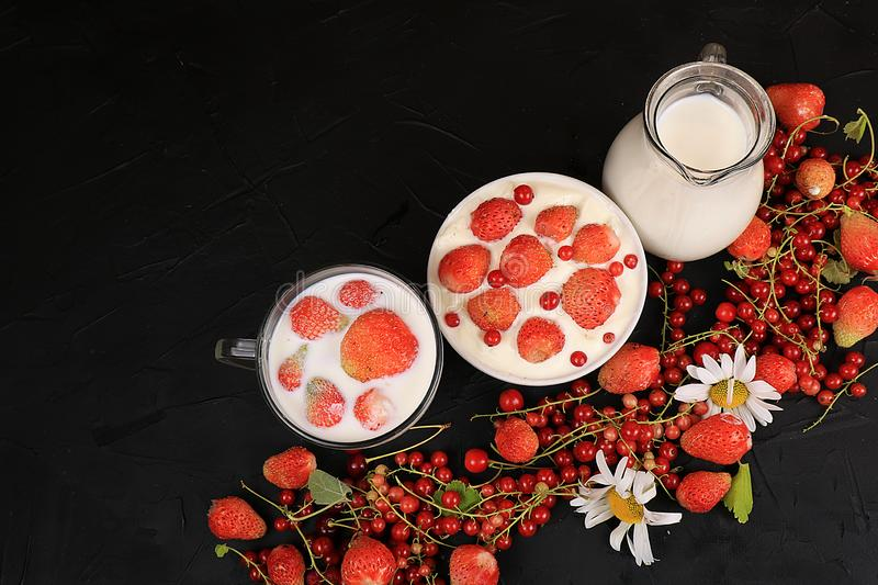 Strawberry yogurt, milk and ripe currant berries and strawberries on a black background royalty free stock photography