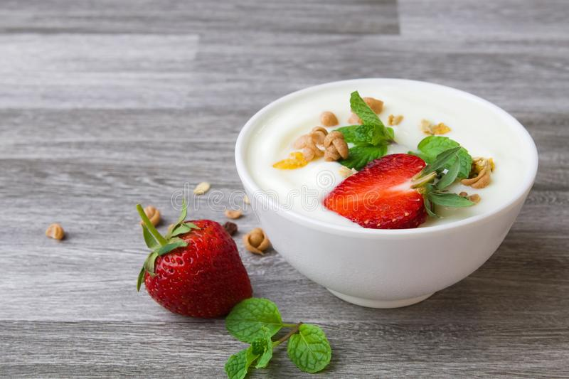 Strawberry with yogurt and mint in bowl on wood. Background stock photography