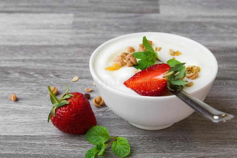 Strawberry with yogurt and mint in bowl on wood. Background stock photo