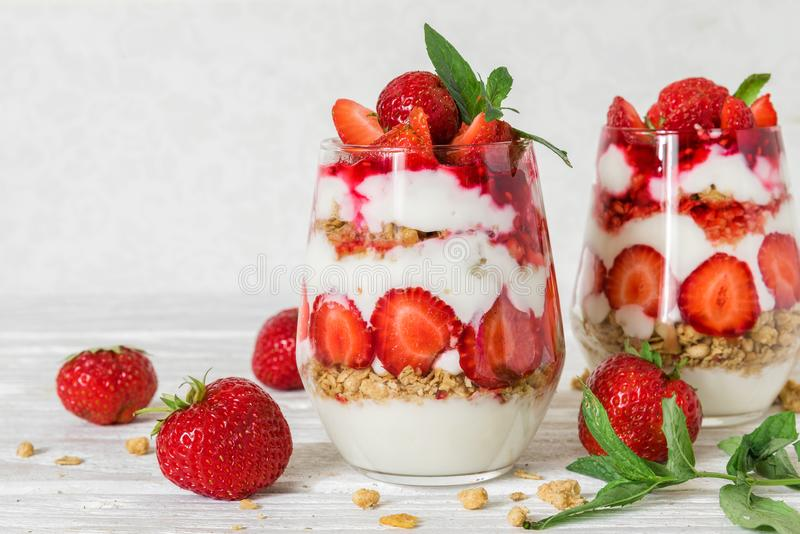 Strawberry yogurt parfait with granola, mint and fresh berries in glasses on white wooden table. healthy breakfast royalty free stock photos
