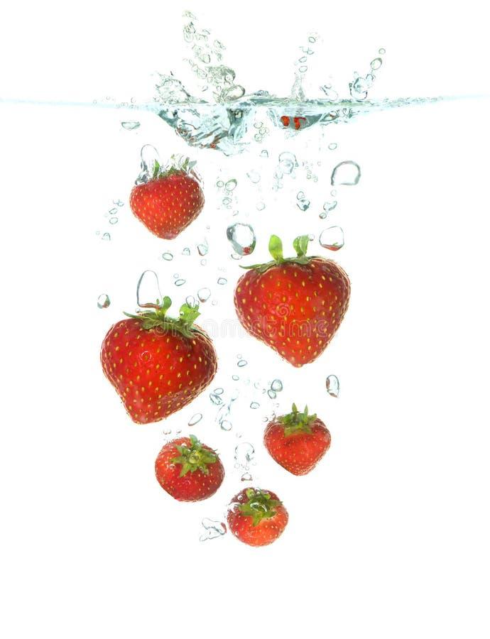 Strawberrys, das in Wasser fällt stockbilder
