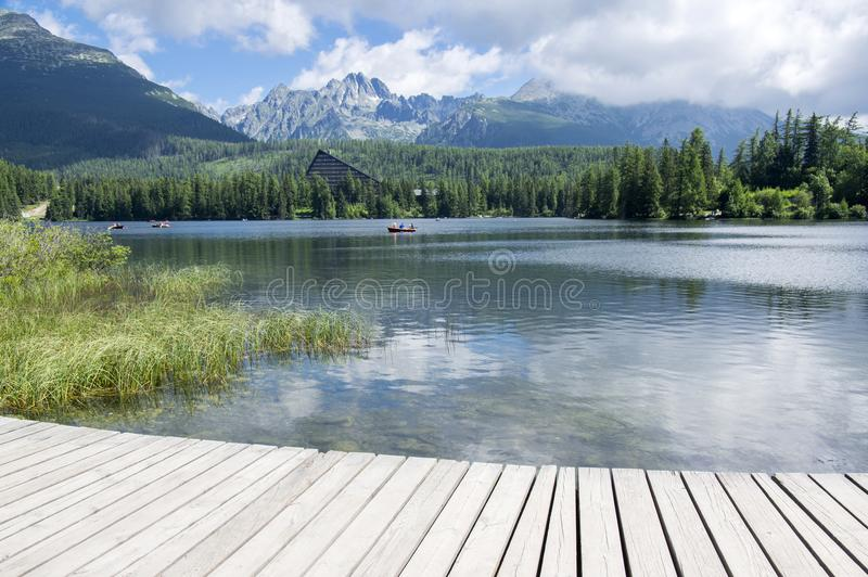 Strbske pleso, High Tatras mountains, Slovakia, early summer morning, lake reflections, wooden pier. Mountain lake royalty free stock photos