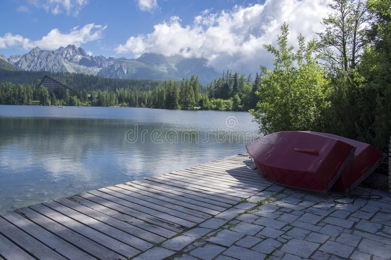 Strbske Pleso, montanhas altas de Tatras, Eslováquia, manhã do início do verão, reflexões do lago, barcos vermelhos fotos de stock