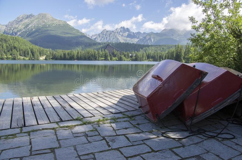 Strbskepleso, Hoge Tatras-bergen, Slowakije, de vroege zomerochtend, meerbezinningen, rode boten op houten pijler royalty-vrije stock afbeelding