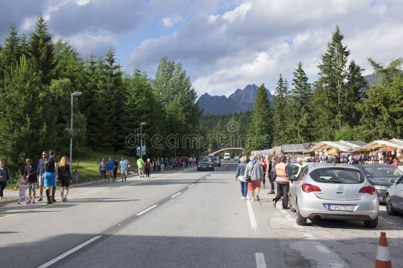 Strbskepleso, Hoge Tatras/Slowakije - Juli 5, 2017: Voetpad en weg aan de bergen met auto's en mensen, mooie dag stock afbeeldingen