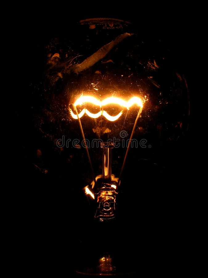 Streak of light. The filament of a bulb lights up in the dark royalty free stock photo
