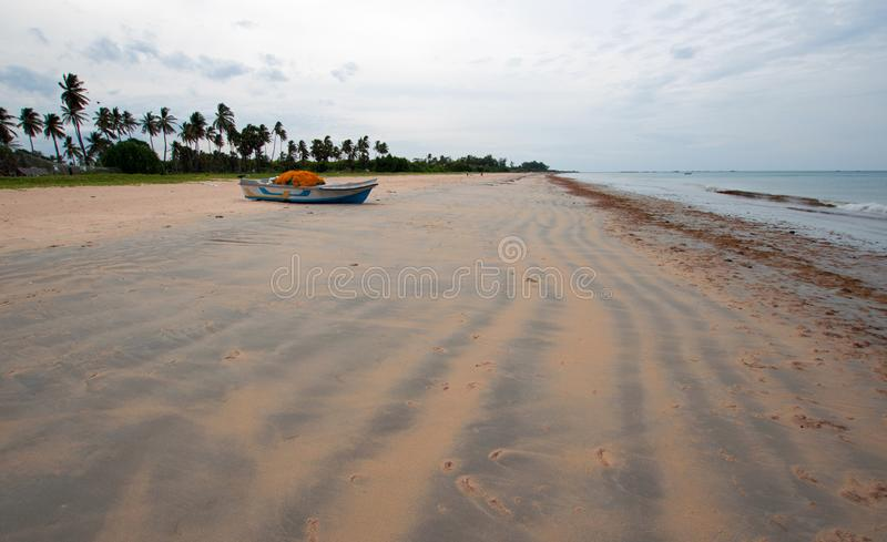 Streaky patterns in sand with boat on Nilaveli beach in Sri Lanka. Asia royalty free stock image