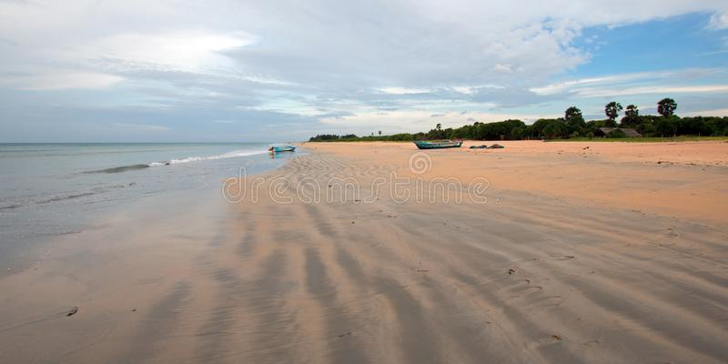 Streaky patterns in sand with boat on Nilaveli beach in Sri Lanka. Asia stock images