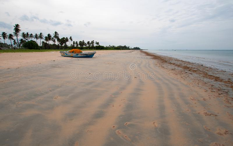 Streaky patterns in sand with boat on Nilaveli beach in Sri Lanka. Asia royalty free stock images