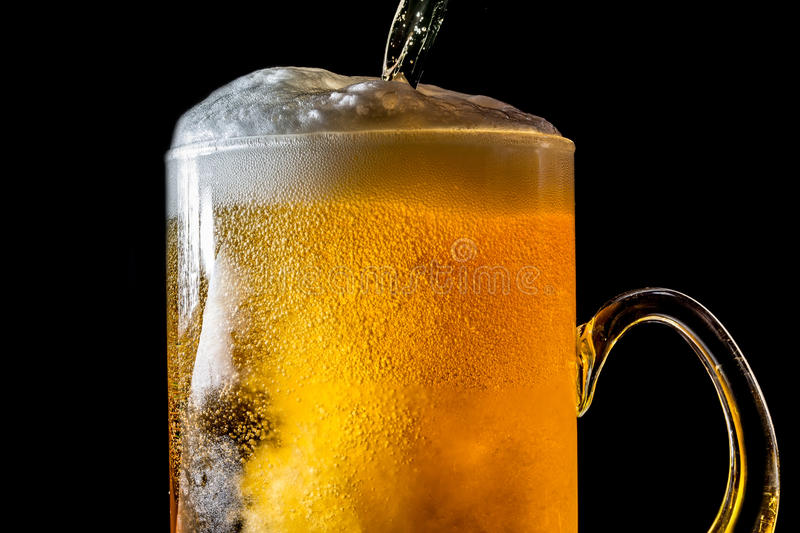 Stream of beer being pouring into a glass with beer and foam isolated on black background, closeup texture. Splashing, splash stock images