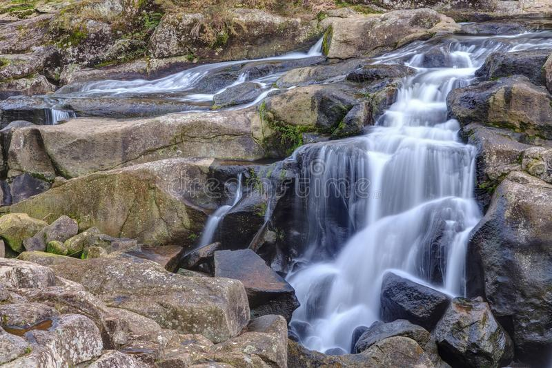 A waterfall flows like a misty veil over rocks. A stream breaks up into multiple waterfalls which cascade down a rocky landscape. The long exposure time makes royalty free stock photo