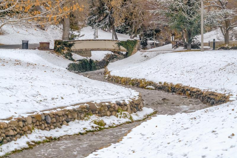 Stream and bridge on a lovely snow covered park in Salt Lake City in winter. The winding stone lined stream passes under a stone bridge with trees in the royalty free stock images
